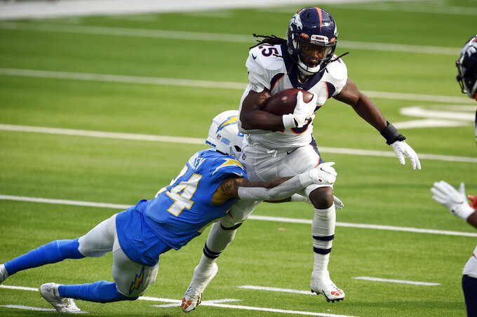Denver Broncos running back Melvin Gordon is tackled by Los Angeles Chargers free safety Nasir Adderley during the first half of an NFL football game Sunday, Dec. 27, 2020, in Inglewood, Calif. (AP Photo/Kelvin Kuo)