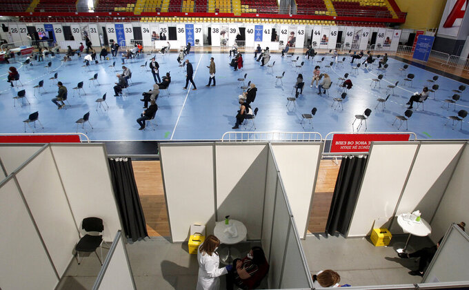 A sports arena has been transformed into a COVID-19 vaccination center, at A1 Arena in Skopje, North Macedonia, on Monday, April 5, 2021. The tiny Balkan country has begun administrating mass immunization of the army, police and media workers on Monday with about 20,000 doses of Russian Sputnic V donated from neighboring Serbia. (AP Photo/Boris Grdanoski)