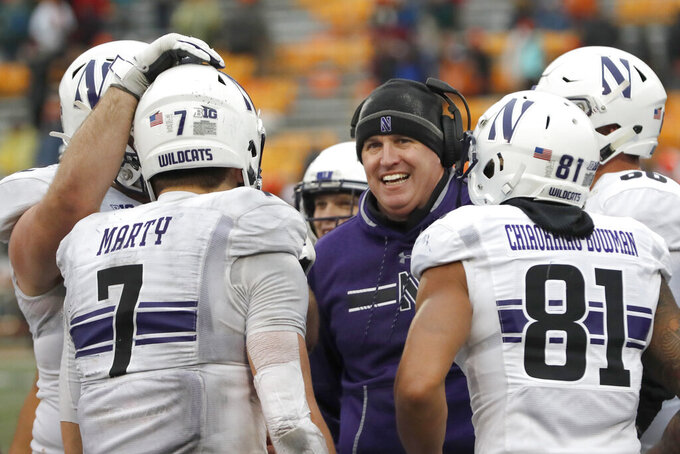 Northwestern head coach Pat Fitzgerald, center, smiles at quarterback Andrew Marty (7) during the closing minutes of the second half of an NCAA college football game against Illinois, Saturday, Nov. 30, 2019, in Champaign, Ill. Northwestern won 29-10. (AP Photo/Charles Rex Arbogast)