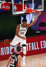 Milwaukee Bucks forward Giannis Antetokounmpo (34) scores a basket in front of Miami Heat guard Duncan Robinson (55) during the first half of an NBA basketball game Thursday, Aug. 6, 2020, in Lake Buena Vista, Fla. (Kim Klement/Pool Photo via AP)