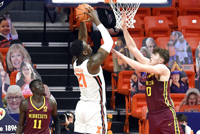 Illinois center Kofi Cockburn (21) goes in for the slam dunk as Minnesota's center Liam Robbins (0) defends in the second half of an NCAA college basketball game Tuesday, Dec. 15, 2020, in Champaign, Ill. (AP Photo/Holly Hart)