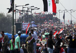 Anti-government protesters stand on barriers set by Iraqi security forces to close the Joumhouriya bridge leading to the Green Zone government areas during ongoing anti-government protests in Baghdad, Iraq, Sunday, Nov. 3, 2019. (AP Photo/Hadi Mizban)