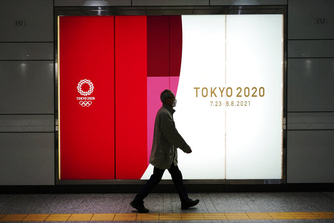 A man wearing a protective mask to help curb the spread of the coronavirus walks near a banner of the Tokyo 2020 Olympics at an underpass in Tokyo Tuesday, Jan. 19, 2021. The Tokyo Olympics are to open in six months on July 23. Interestingly, Tokyo organizers have no public program planned to mark the milestone. There is too much uncertainty for that right now. (AP Photo/Eugene Hoshiko)