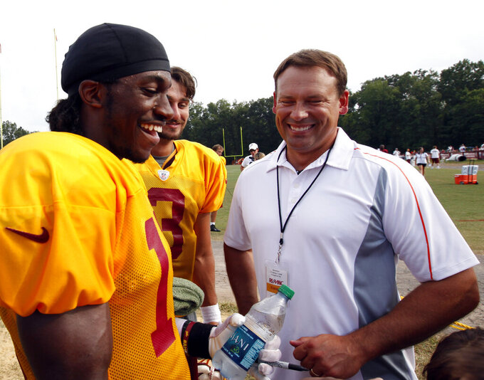 FILE - In this Aug. 3, 2012, file photo, Washington Redskins quarterback Robert Griffin III, left, laughs with quarterback Jonathan Crompton, center, and former Redskins quarterback Rep. Heath Shuler, D-N.C., after an NFL football training camp practice at Redskins Park in Ashburn, Va. Shuler started only 13 games for the Redskins after being the third overall pick in 1994; Washington got one playoff appearance out of Griffin after taking him second overall in 2012. (AP Photo/Alex Brandon, File)