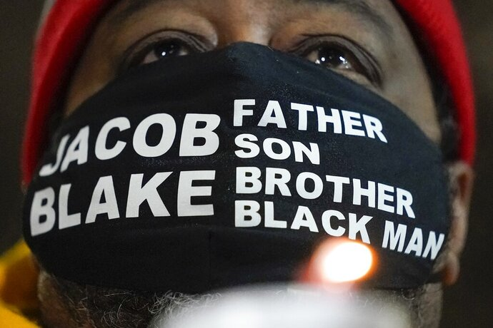 Jacob Blake Sr., father of Jacob Blake, holds a candle at a rally Monday, Jan. 4, 2021, in Kenosha, Wis. (AP Photo/Morry Gash)