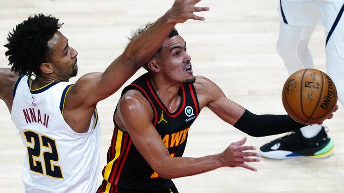Atlanta Hawks guard Trae Young (11) goes past Denver Nuggets forward Zeke Nnaji (22) to score during the second half of an NBA basketball game Sunday, Feb. 21, 2021, in Atlanta. (AP Photo/John Bazemore)