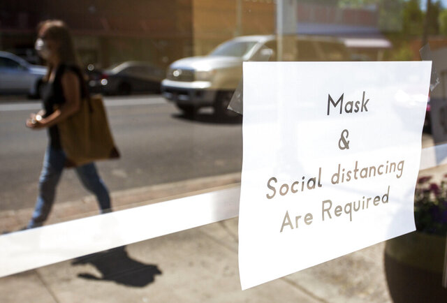 A woman wearing a mask walks past in sign on the door at Pullman Foursquare Church on Thursday, June 25, 2020, in downtown Pullman, Wash. Washington Gov. Jay Inslee announced that masks will be required in public starting on Friday to help prevent the spread of the coronavirus. (Geoff Crimmins/The Moscow-Pullman Daily News via AP)