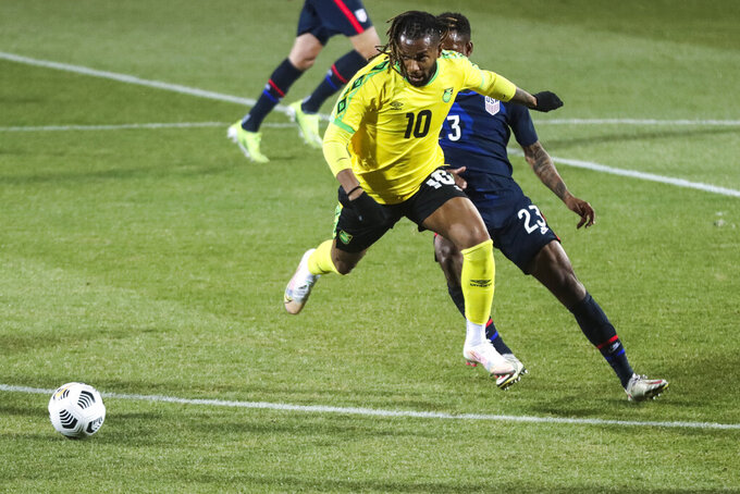 Jamaica's Kasey Palmer, foreground, duels for the ball with USA's Kellyn Acosta during  the international friendly soccer match between USA and Jamaica at SC Wiener Neustadt stadium in Wiener Neustadt, Austria, Thursday, March 25, 2021. (AP Photo/Ronald Zak)