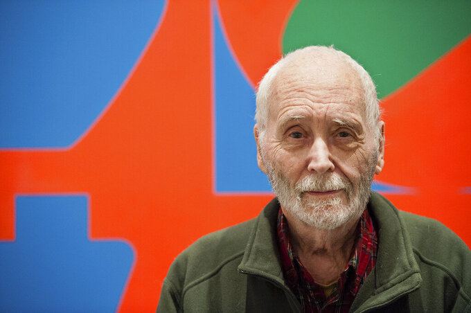 """FILE - In this Sept. 24, 2013, file photo, artist Robert Indiana, known for his """"LOVE"""" artwork series, poses in front of that painting at New York's Whitney Museum of American Art. Indiana's estate has reached a settlement that keeps intact a longstanding relationship with the copyright holder of the iconic """"LOVE"""" series. Officials said Friday, June 11, 2021, that New York-based Morgan Art Foundation will work with the Maine-based Star of Hope Foundation, which aims to transform Indiana's island home in Maine into a museum. (AP Photo/Lauren Casselberry, File)"""