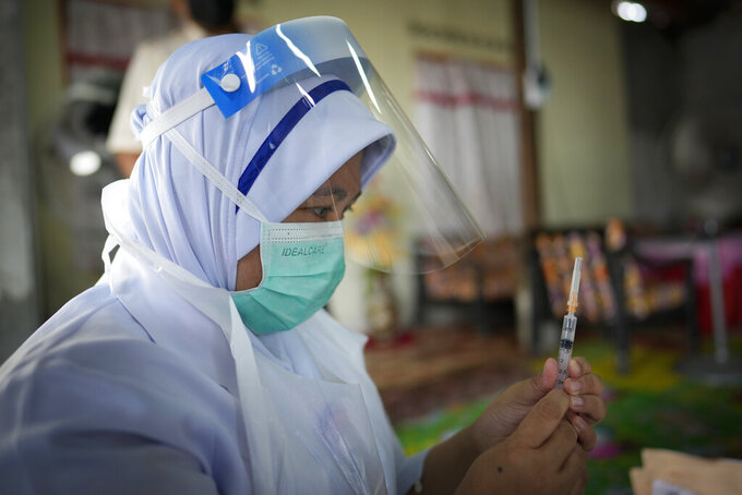 A nurse prepares to administer a Pfizer COVID-19 vaccine to an elderly woman in her house in rural Sabab Bernam, central Selangor state, Malaysia, Tuesday, July 13, 2021. Medical teams are going house to house in rural villages to reach out to elderly citizens as the government seeks to ramp up its vaccination program. Despite a strict lockdown, the pandemic has worsened with more than 844,000 confirmed cases nationwide and over 6,200 deaths. (AP Photo/Vincent Thian)