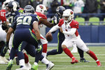 Arizona Cardinals quarterback Kyler Murray, right, keeps the ball away from the Seattle Seahawks during the first half of an NFL football game, Sunday, Dec. 22, 2019, in Seattle. (AP Photo/Elaine Thompson)