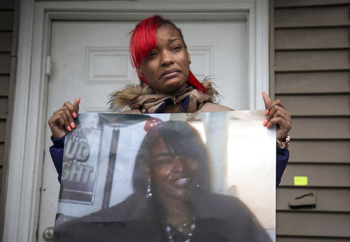 FILE - In this Sunday, Dec. 27, 2015 file photo, Latonya Jones, 19, holds a photo of her mother, Bettie Jones, during a vigil in Chicago. A Chicago police officer who fatally shot Bettie Jones while firing at a neighbor he claimed was swinging a bat at him was fired Thursday, Oct. 17, 2019  by the city's police oversight board.  (Ashlee Rezin/Chicago Sun-Times via AP, File)