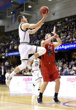 Wofford guard Fletcher Magee (3) drives the ball to the basket against VMI forward Tyler Creammer (25) in the first half of an NCAA college basketball game for the Southern Conference basketball tournament championship, Saturday, March 9, 2018, in Asheville, N.C. (AP Photo/Kathy Kmonicek