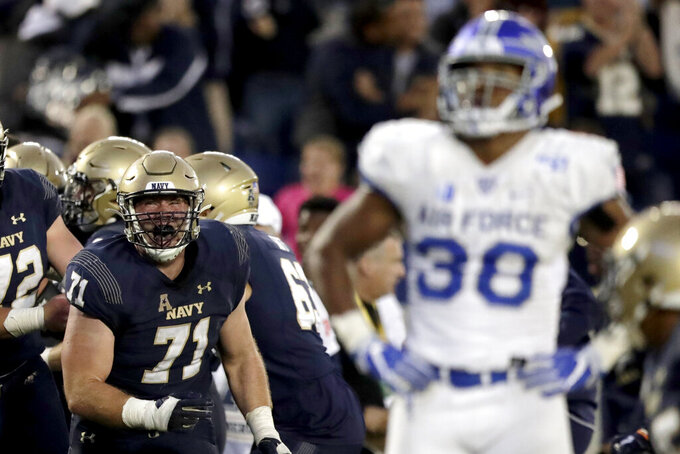 Navy offensive tackle Billy Honaker, left, reacts after teammate quarterback Malcolm Perry scored a touchdown run against Air Force during the second half of an NCAA college football game Saturday, Oct. 5, 2019, in Annapolis, Md. Navy won 34-25. (AP Photo/Julio Cortez)