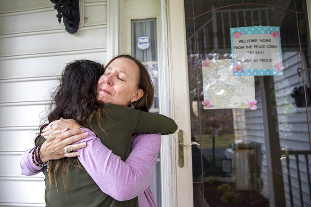 Holly Balcom, 54, hugs her daughter Kelsea Mensh, 22, as they reunite at their home in Dumfries, Va., Wednesday, April 1, 2020, after Mensh, who had served a year in the Peace Corps in the Dominican Republic, finished her 2 week quarantine period. After evacuating her from her post, the Peace Corps put Mensh up in a hotel in her hometown to self-isolate so that she wouldn't cause any risk to her mother, who is a cancer survivor and has viral induced asthma. Though she is grateful to have been evacuated,