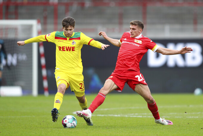 Union's Grischa Proemel, right, and Cologne's Elvis Rexhbecaj, left, challenge for the ball during the German Bundesliga soccer match between 1. FC Union Berlin and 1. FC Cologne in Berlin, Germany, Saturday, March 13, 2021. (Andreas Gora/dpa via AP)