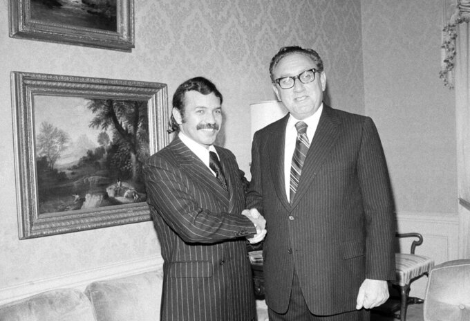 FILE - In this Oct. 1, 1975, file photo Abdelaziz Bouteflika, left, meets with U.S. Secretary of State Henry Kissinger at the U.S. State Department suite at the Waldorf Astoria Hotel Towers, in New York. Former Algerian President Bouteflika, who fought for independence from France in the 1950s and 1960s and was ousted amid pro-democracy protests in 2019 after 20 years in power, has died at age 84, state television announced Friday, Sept. 17, 2021.  (AP Photo/Dave Pickoff, File)