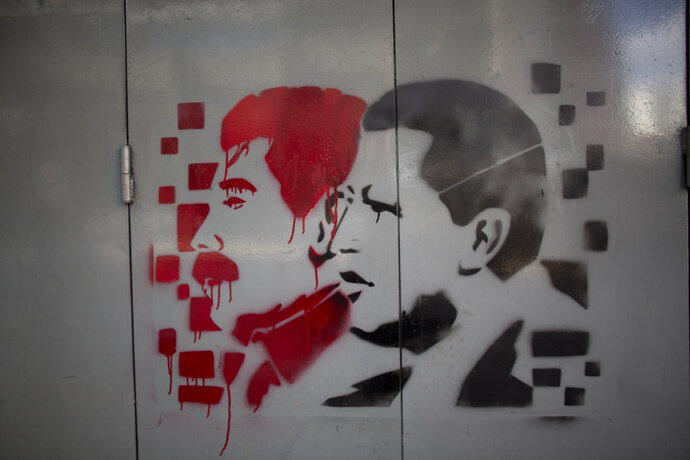 A gate is covered with images of Venezuela's late President Hugo Chavez, right, and current President Nicolas Maduro, ahead of the presidential election in Caracas, Venezuela, Wednesday, May 16, 2018. Leading opposition parties are boycotting the May 20 presidential race, leaving as Maduro's main challenger a one-time Chavez acolyte, Henri Falcon, who many suspect is in the government's pocket and wouldn't be allowed to take office even if he were somehow able to prevail. (AP Photo/Ariana Cubillos)
