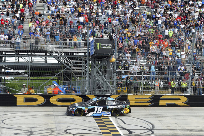 Driver Martin Truex Jr. (19) crosses the finish line to win the NASCAR Cup Series auto race, Monday, May 6, 2019, at Dover International Speedway in Dover, Del. (AP Photo/Will Newton)