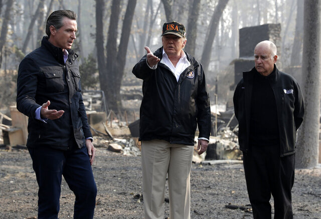 FILE - In this Nov. 17, 2018 file photo President Donald Trump talks with Gov.-elect Gavin Newsom, left, and as California Gov. Jerry Brown listens during a visit to a neighborhood impacted by the wildfires in Paradise, Calif. Newsom and Trump, who are often critical of each other, are getting along during the coronavirus pandemic. (AP Photo/Evan Vucci, File)