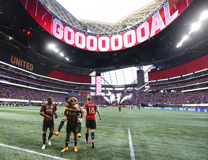 FILE - In this June 2, 2018, file photo, the roof of Mercedes-Benz Stadium is open as Atlanta United forward Josef Martinez celebrates his goal against the Philadelphia Union on a penalty kick while Miguel Almiron jumps on his back during an MLS soccer match in Atlanta. The 2026 World Cup will return to the U.S. for the first time since 1994. Atlanta's new Mercedes-Benz Stadium was shown prominently in the video used in the North American pitch for the bid. (Curtis Compton/Atlanta Journal-Constitution via AP, File)/