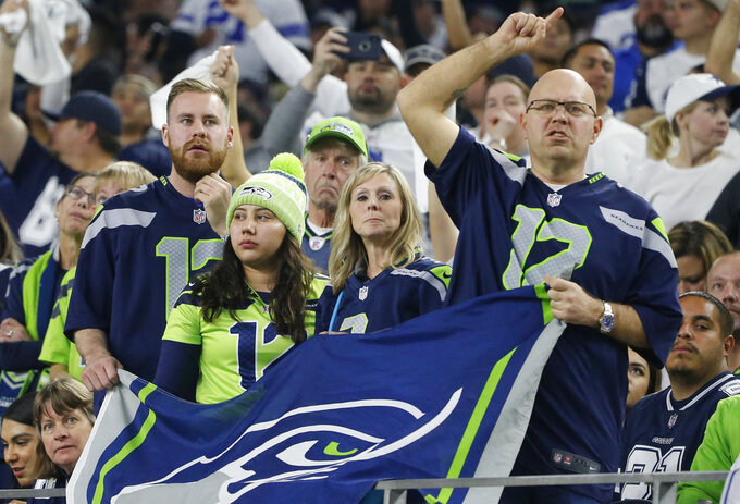Seattle Seahawks fans cheer against the Dallas Cowboys during the first half of the NFC wild-card NFL football game in Arlington, Texas, Saturday, Jan. 5, 2019. (AP Photo/Michael Ainsworth)