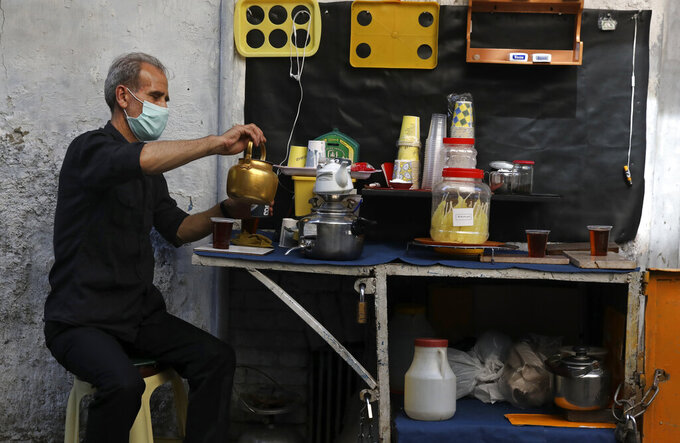 A vendor prepares tea at the Grand Bazaar, in Tehran, Iran, Thursday, June 3, 2021. Iran's ailing economy is the major concern for those living in the Islamic Republic ahead of the country's presidential election. They face a daily grinding nightmare of high inflation, an ever-weakening national currency and high unemployment exacerbated by the coronavirus pandemic. (AP Photo/Vahid Salemi)
