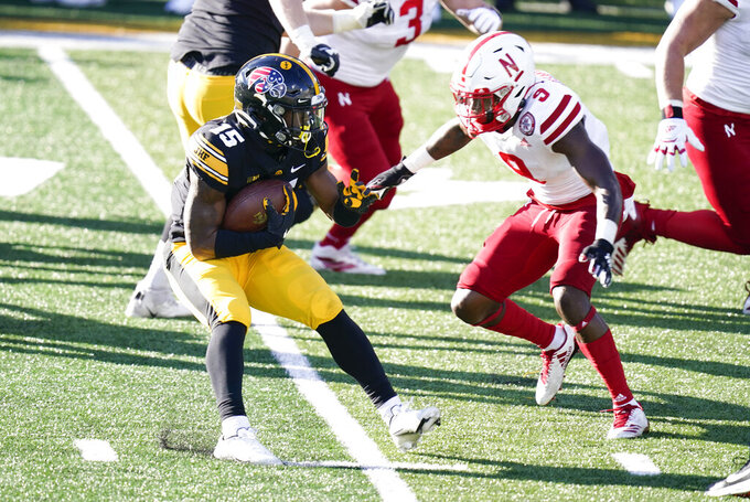 Iowa running back Tyler Goodson, left, runs from Nebraska safety Marquel Dismuke (9) during the second half of an NCAA college football game, Friday, Nov. 27, 2020, in Iowa City, Iowa. Iowa won 26-20. (AP Photo/Charlie Neibergall)