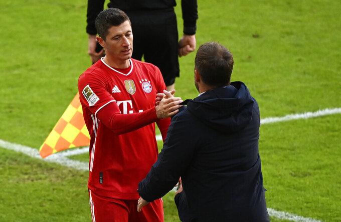 Bayern's Robert Lewandowski, left, shake hands with Bayern's head coach Hans-Dieter Flick during the German Bundesliga soccer match between FC Bayern Munich and VfB Stuttgart in Munich, Germany, Saturday, March 20, 2021. (Matthias Balk/Pool via AP)