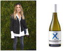 This combination photo shows actress Sarah Jessica Parker at the 2018 Chanel Tribeca Film Festival Women Filmmakers Luncheon in New York on April 20, 2018, left, and a bottle of her new sauvignon blanc, X SJP. . (AP Photo, left, and Invivo & Co. via AP)