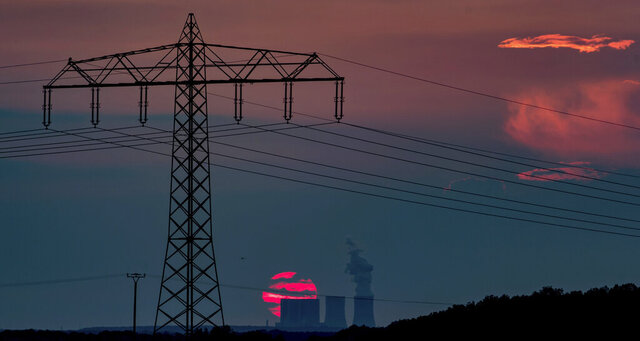 The red ball of the sun sets behind the towers of the Lippendorf power plant, in Neukieritzsch south of Leipzig, Germany, Friday, June 26, 2020. (Hendrik Schmidt/dpa via AP)