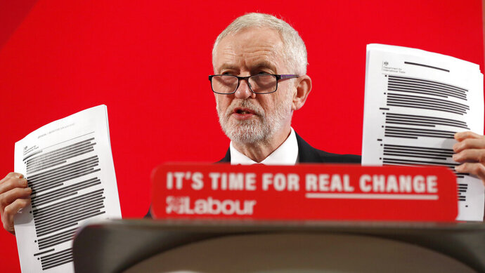 Britain's Labour party leader Jeremy Corbyn shows blacked out papers as he delivers a speech in London, England, Wednesday, Nov. 27, 2019, ahead of the general election on Dec. 12. (AP Photo/Frank Augstein)