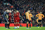 Referee Anthony Taylor, 2nd left, gestures while players wait for the VAR decision on Liverpool's opening goal during the English Premier League soccer match between Liverpool and Wolverhampton Wanderers at Anfield Stadium, Liverpool, England, Sunday Dec. 29, 2019. (AP Photo/Jon Super)