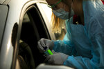 FILE - In this Aug. 24, 2020, file photo, Lindsey Helkenn, a medical lab technician from Spearfish, conducts a COVID-19 test in Sturgis, S.D. A surge of coronavirus cases in Wisconsin and the Dakotas is forcing a scramble for hospital beds and raising political tensions, as the Upper Midwest and Plains emerge as one of the nation's most troubling hotspots. (Grace Pritchett/Rapid City Journal via AP, File)