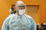 Brant McAdams, head football coach at Pacific Lutheran, wears personal protective equipment as he administers COVID-19 tests for student athletes Wednesday, Feb. 3, 2021, on campus in Tacoma, Wash. There was never a chapter in any of the books on becoming a small NCAA college football coach that addressed administering COVID-19 tests in the midst of a pandemic, but now it's something he's doing to give his players the chance at a season. (AP Photo/Ted S. Warren)