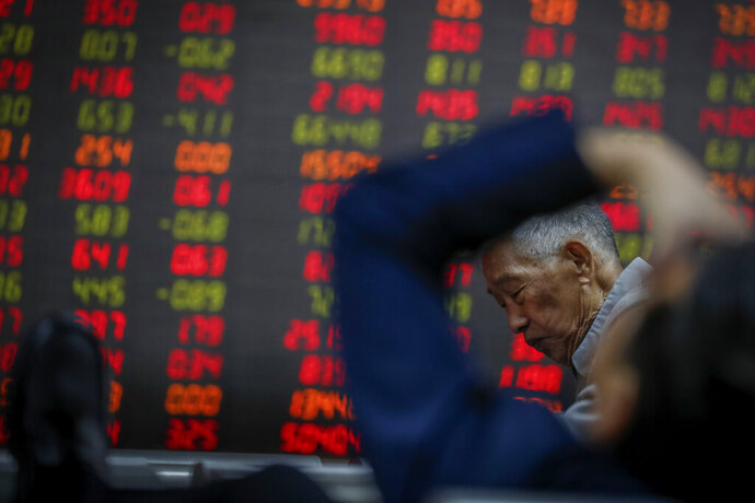 Chinese investors react as they monitor stock prices at a brokerage house in Beijing, Wednesday, Oct. 16, 2019. Asian shares were higher Wednesday after a gain on Wall Street boosted by healthy earnings reports from U.S. companies. (AP Photo/Andy Wong)