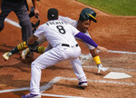 Oakland Athletics' Tony Kemp (5) avoids the tag at home plate by Colorado Rockies third baseman Josh Fuentes (8) during the third inning of a baseball game, Wednesday, Sept. 16, 2020, in Denver. (AP Photo/Jack Dempsey)