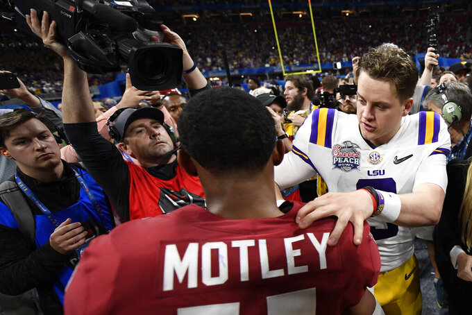 LSU quarterback Joe Burrow (9) speaks with Oklahoma cornerback Parnell Motley (11) after the Peach Bowl NCAA semifinal college football playoff game, Saturday, Dec. 28, 2019, in Atlanta. LSU won 63-28. (AP Photo/Danny Karnik)