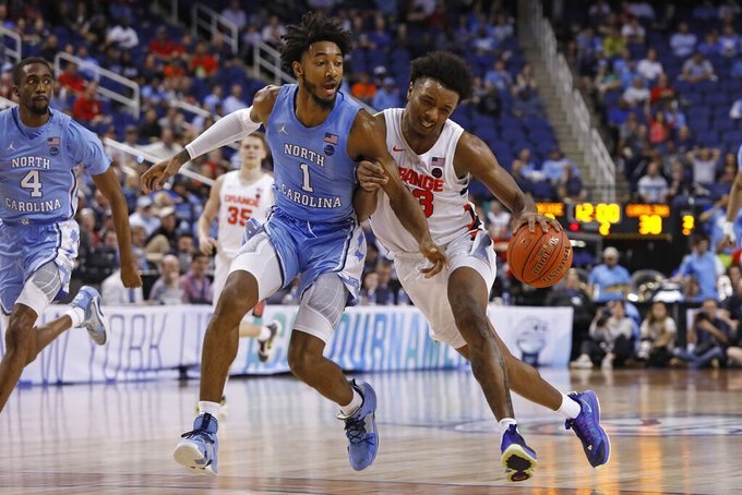 North Carolina guard Leaky Black (1) guards Syracuse forward Elijah Hughes (33) during the second half of an NCAA college basketball game at the Atlantic Coast Conference tournament in Greensboro, N.C., Wednesday, March 11, 2020. (AP Photo/Ben McKeown)