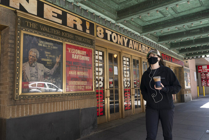 A woman walks past the Walter Kerr Theatre, Thursday, May 6, 2021, in New York where Hadestown was showing before the coronavirus pandemic forced its closing a year ago. Gov. Andrew Cuomo has announced that Broadway theaters can reopen Sept. 14, 2021. (AP Photo/Mark Lennihan)