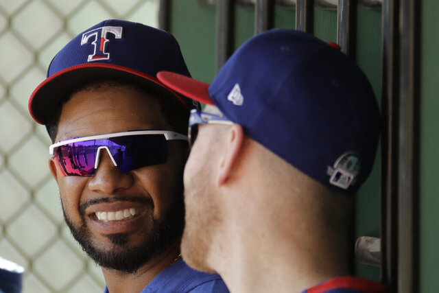 Texas Rangers' Elvis Andrus, left, talks with Todd Frazier during spring training baseball practice Monday, Feb. 17, 2020, in Surprise, Ariz. (AP Photo/Charlie Riedel)
