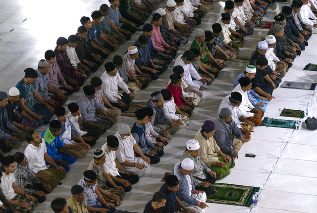 In this Tuesday, April 28, 2020, photo, Muslims men attend a Ramadan evening prayer at a mosque in Lhokseumawe, in Indonesia's Aceh province. Muslim leaders in the province that practices Shariah law are allowing mass prayers in mosques if certain health protocols are in place. (AP Photo/Zik Maulana)
