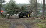 In this Wednesday, Jan. 8, 2020 photo a tractor lifts a tree at the site of the planned new Tesla Gigafactory in Gruenheide near Berlin, Germany. Tesla CEO Elon Musk said during an awards ceremony in Berlin in November 2019 that 'we have decided to put the Tesla Gigafactory Europe in the Berlin area.' The company will also set up an engineering and design center in Berlin, Musk said. He wrote on Twitter that the new plant 'will build batteries, powertrains & vehicles, starting with Model Y.' (AP Photo/Michael Sohn)
