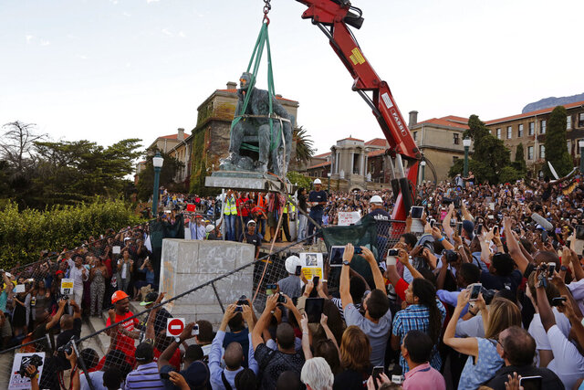 FLE - In this April 9, 2015, file photo, cheering students surround a statue of British colonialist Cecil Rhodes, as it is removed from the campus at the Cape Town University, Cape Town, South Africa. New campaigns in the U.S. and Europe to pull down monuments to slave traders and colonial rulers are now following Africa's lead. (AP Photo/Schalk van Zuydam, File)
