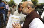 FILE - In this Monday, Aug. 5, 2019, file photo, Indian Home Minister Amit Shah arrives at the Parliament carrying a copy of a confidential document that lists out the procedure for revoking Kashmir's special status in New Delhi, India. Shah says normalcy has returned in most areas in Indian-controlled Kashmir but the detention of politicians and the blockade of the internet and social media are continuing because of security concerns. Asked by lawmakers in Parliament on Wednesday, Nov. 20, how soon the restrictions are likely to be lifted, Shah says authorities have to fix priorities when it comes to security and the fight against terrorism. India stripped the region of its semi-autonomous powers and implemented a strict clampdown on Aug. 5. (AP Photo/Manish Swarup, File)