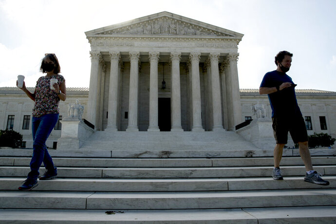 Two people walk down the steps outside the Supreme Court, Thursday, July 9, 2020, in Washington. (AP Photo/Andrew Harnik)