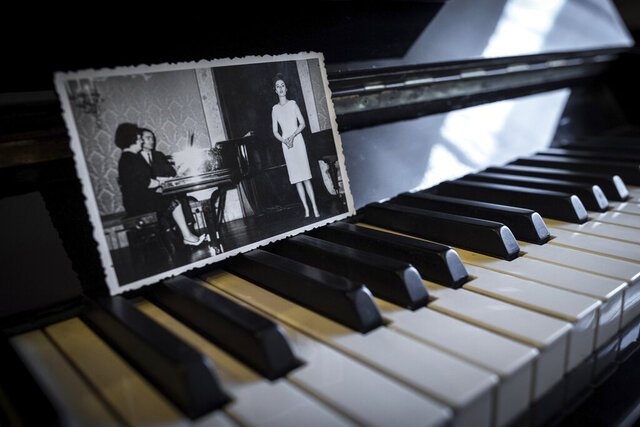 In this picture taken, April 26, 2020, a family album photograph showing Hannelore Fischer Cruz singing is placed on her piano at the house where she used to live in Braga, northern Portugal. Born amid the ruins of wartime Vienna, Hannelore Fischer was sent as a small child to Portugal where her flamboyant manner and outstanding soprano voice would later help her build a life far from her place of birth. She died of COVID-19 on March 25, 2020, after four days on a ventilator at Braga's hospital. (AP Photo/Luis Vieira)