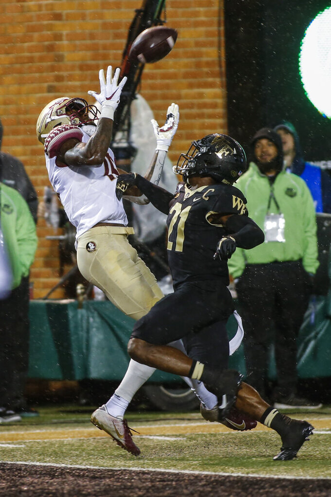 FILE - In this Saturday, Oct. 19, 2019, file photo, Florida State wide receiver Tamorrion Terry, left, catches a touchdown pass against Wake Forest defensive back Essang Bassey in the second half of an NCAA college football game in Winston-Salem, N.C. On Wednesday, Nov. 11, 2020, head coach Mike Norvell announced that leading wide receiver Tamorrion Terry has left the team. (AP Photo/Nell Redmond, File)