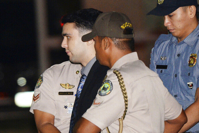 FILE - In this Dec. 1, 2015, file photo, convicted U.S. Marine Lance Cpl. Joseph Scott Pemberton is escorted to his detention cell upon arrival at Camp Aguinaldo at suburban Quezon city, northeast of Manila, Philippines. The Philippine president pardoned the U.S. Marine on Monday, Sept. 7, 2020 in a surprise move that will free him from imprisonment in the 2014 killing of a transgender Filipino woman that sparked anger in the former American colony. (Ted Aljibe/Pool Photo, File)