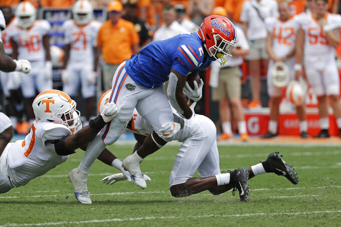 Florida running back Lamical Perine, center, runs for yardage before he is stopped by Tennessee linebacker Quavaris Crouch, left, and defensive back Warren Burrell, bottom right, during the first half of an NCAA college football game, Saturday, Sept. 21, 2019, in Gainesville, Fla. (AP Photo/John Raoux)